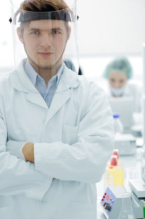 Confident young doctor with mask and folded hands in hospital laboratory photo