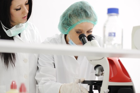 Two female scientists working at the laboratory with microscope Stock Photo - 10087165