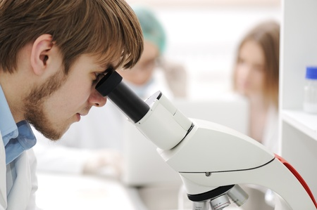 group of the students working at the laboratory with microscope photo