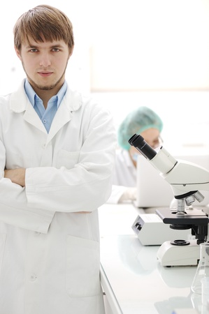 serious doctor: Two scientists working at the laboratory with microscope