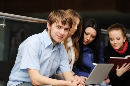 Young group of students working together with laptop and books Stock Photo - 10087238