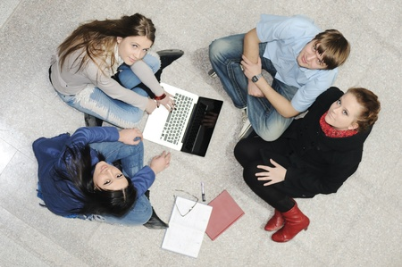 sitting on the ground: Creative group of students sitting and working together Stock Photo