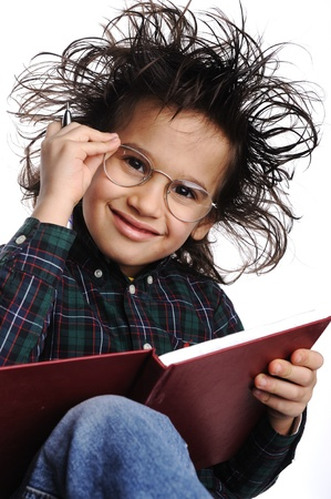 young boy smiling: Smart nerd kid with glasses and funny hair writing