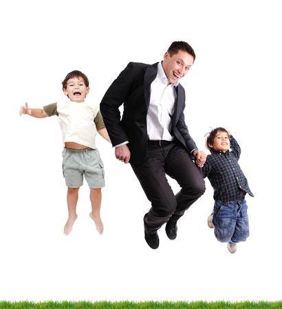 niños latinos: Padre e hijos saltando sobre hierba verde, aislado