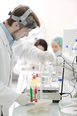 Group of the students working at the laboratory with liquids in tubes and electronics Stock Photo - 10087106