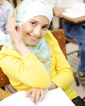 learning arabic: Cute Muslim arabic girl sitting on the chair and holding pencil - at school