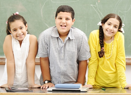 learning arabic: Three happy children standing at board, posing beside the table Stock Photo