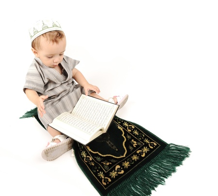 learning arabic:  little muslim kid is praying on traditional way