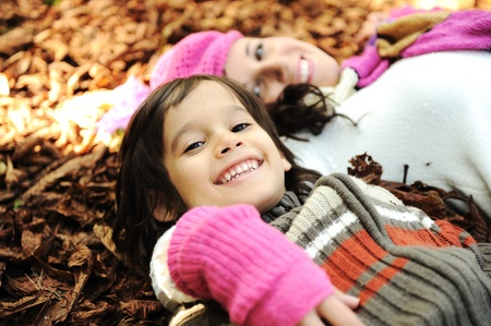 Cute boy lying in the Autumn fall leaves with his mother photo