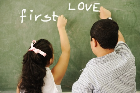 first love: First love - boy and girl writing on board in classroom Stock Photo