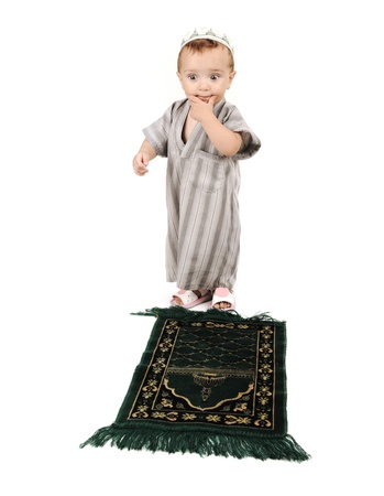 little muslim kid is praying on traditional way and thinkig how Stock Photo - 10290127