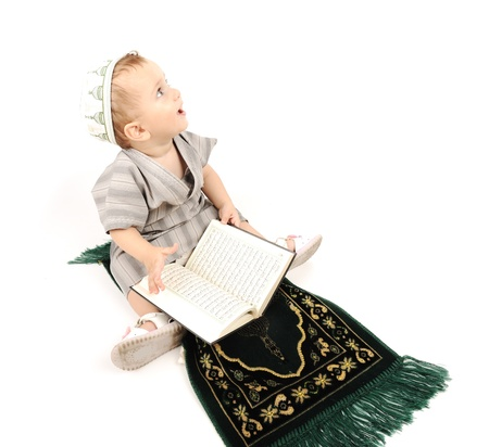 moslem:  little muslim kid is praying on traditional way and looking up Stock Photo