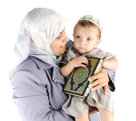 learning arabic: Muslim mother and her little son holding a Koran