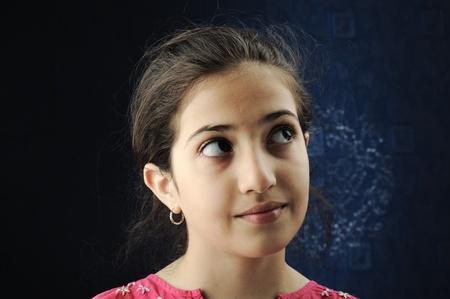 black youth: Little beautiful arabic Muslim girl sitting at window, portrait Stock Photo