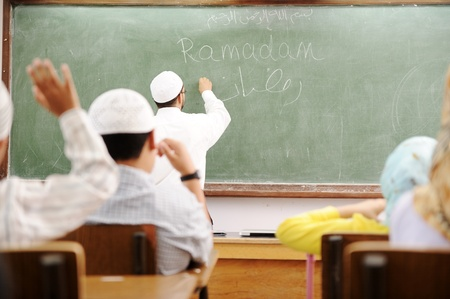 Teacher at classroom writing Ramadan on board Stock Photo - 10290810