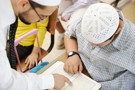 Education activities in classroom at school, Muslim teacher showing Koran to kid photo