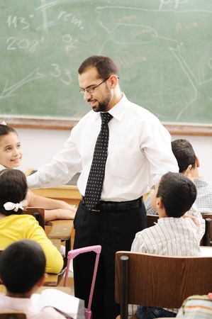 teacher in class: Education activities in classroom at school, happy children learning Stock Photo