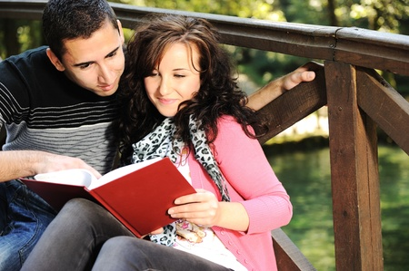 young loving couple, boy and girl on the bridge on river  in park studying together photo