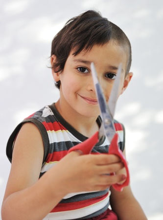 Kid cutting hair to himself with scissors, funny look photo