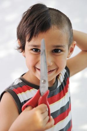 coupe de cheveux homme: Couper les cheveux Kid lui-m�me avec des ciseaux, dr�le d'air Banque d'images