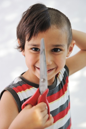 beauty salon face: Kid cutting hair to himself with scissors, funny look