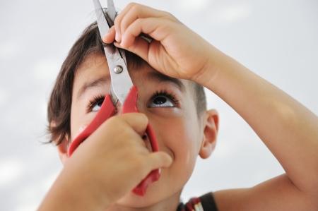 comb hair: Kid tagliare i capelli a se stesso con le forbici, sguardo divertente Archivio Fotografico