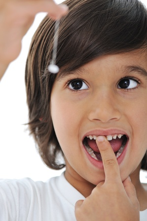 tooth fairy: Lost milk tooth, cute boy with long hair Stock Photo