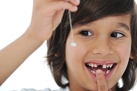 Lost milk-tooth, cute boy with long hair holding his tooth on thread photo