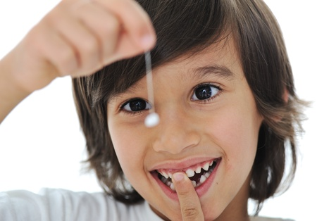 tooth fairy: Lost milk-tooth, cute boy with long hair holding his tooth on thread