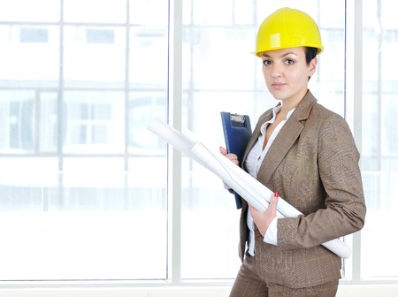 architect woman in business suit portrait with yellow helmet and blueprints photo