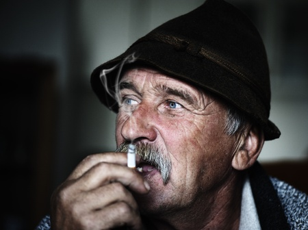 Closeup Artistic Photo of Aged Man With  Grey Mustache Smoking, grain added photo