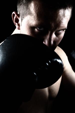 Artistic portrait of attractive boxer against black background photo