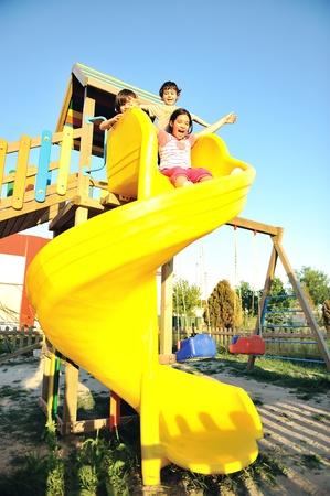 niños en area de juegos: los niños que juegan en el control deslizante