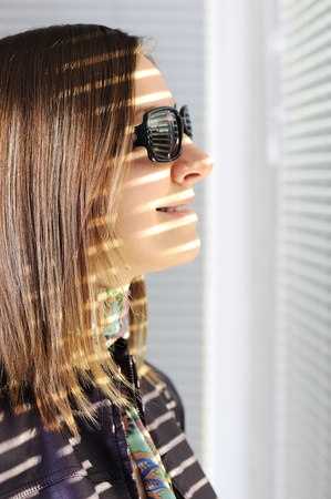looking through window: Young brunette woman in the sunlight looking through  jalousie on window Stock Photo