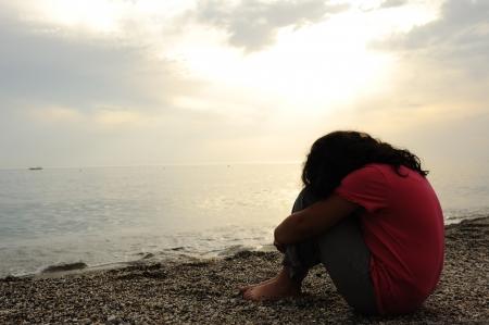 verdrietig meisje: Lonely verdrietig meisje op de donkere strand Stockfoto