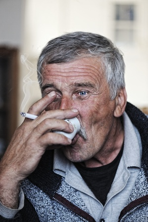 Old man with mustache smoking cigarette and drinking coffee photo