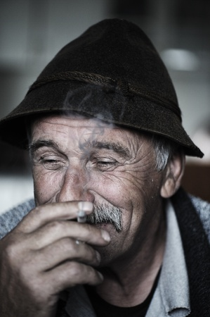 mature old generation: Closeup Artistic Photo of Aged Man With  Grey Mustache Smoking Cigarette