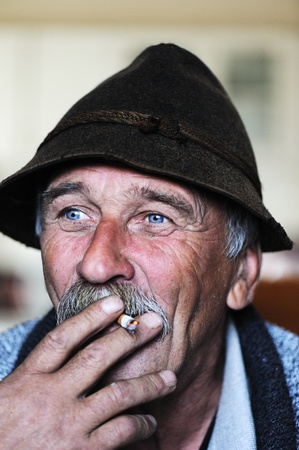 70 year old man: Closeup Artistic Photo of Aged Man With  Grey Mustache Smoking Cigarette