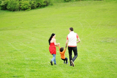 green back: running family on green meadow in nature