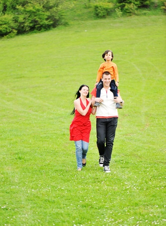 running family on green meadow in nature photo
