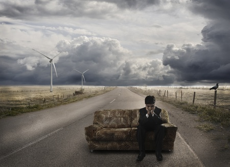 business concern: Young businessman waiting on sofa, at the road, disappointed