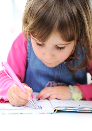 Happy little girl drawing with pencils at home photo