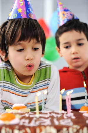 Two little boys blowing candles on cake, happy birthday party photo