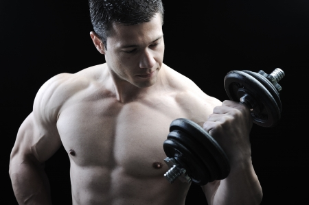 The Perfect male body - Awesome bodybuilder posing with dumbbells photo