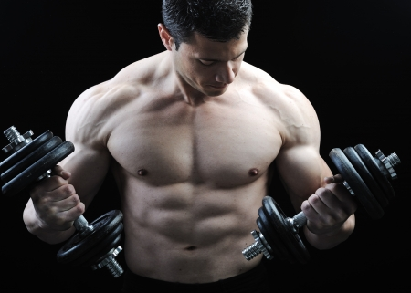 levantando pesas: El cuerpo masculino perfecto - culturista impresionante posando con pesas Foto de archivo