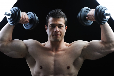 pectoral: The Perfect male body - Awesome bodybuilder posing with dumbbells Stock Photo