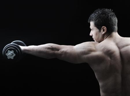 levantando pesas: El cuerpo perfecto hombre - culturista posando impresionante