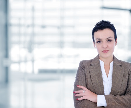 Business woman standing casually against modern building, folded hands photo