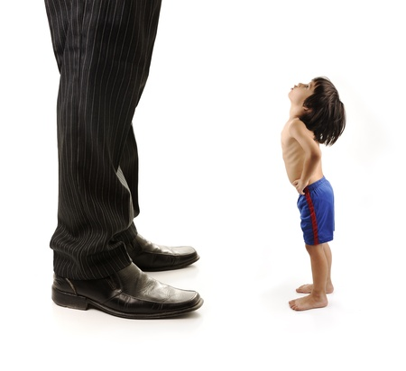 giant: Little small child  is looking at the giant legs of  businessman adult