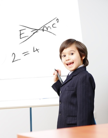 Genius little boy writting E=mc2 on the board, new formula instead, conceptual idea photo